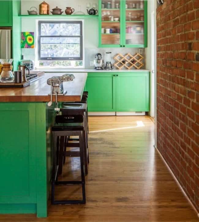 Cozinha verde com tijolos à vista
