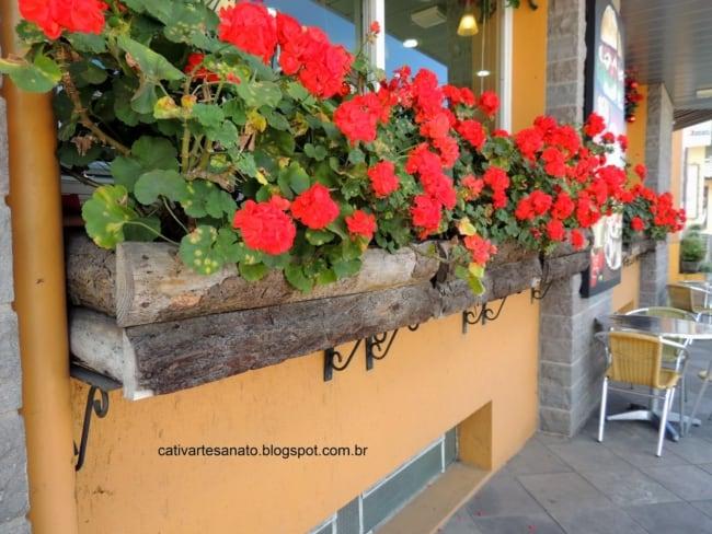 Floreira rústica de madeira com flores vermelhas