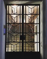 Porta de ferro com formas geométricas e placas de vidro