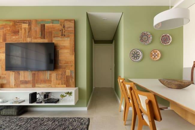 Sala de estar e jantar com parede verde