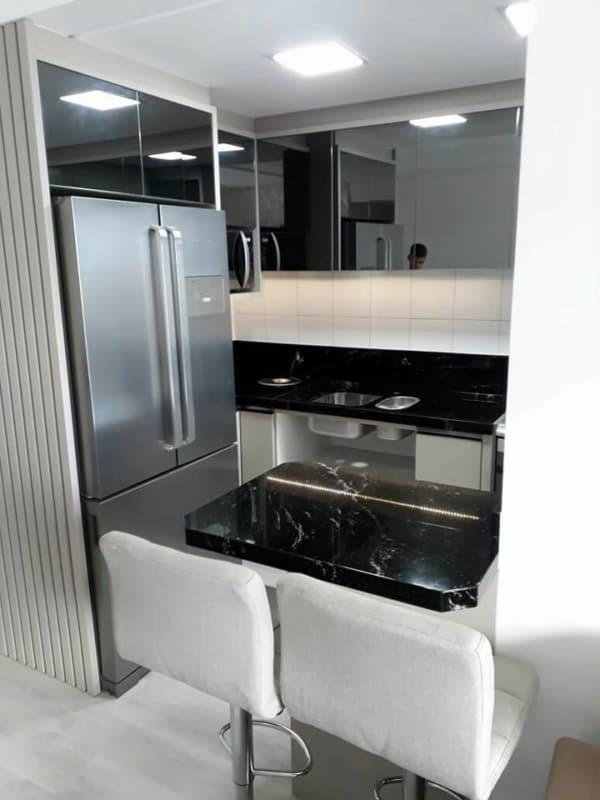 cozinha de apartamento com balcão de mármore preto