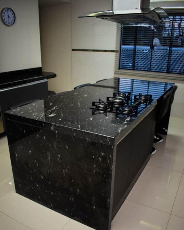ilha com mármore preto e cooktop