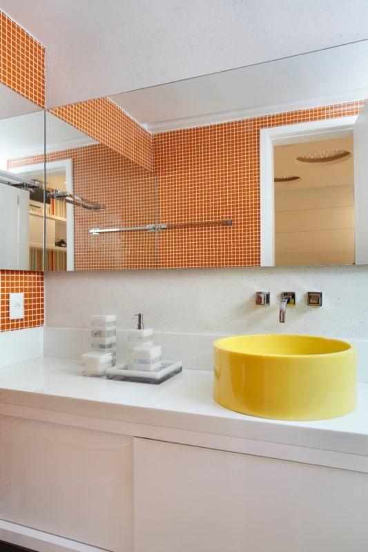 Banheiro com pastilhas laranjas e cuba amarela