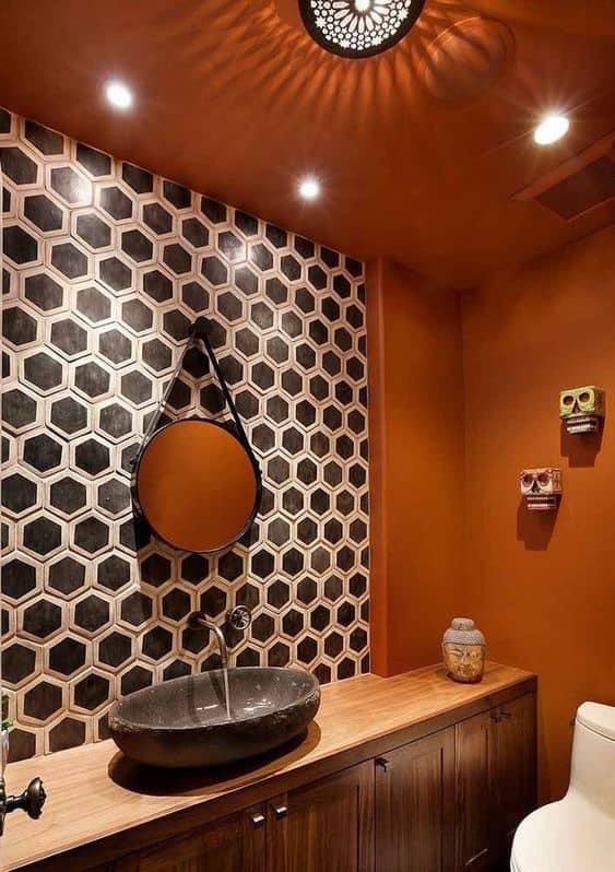 Banheiro estiloso com estampa geométrica e parede cor laranja