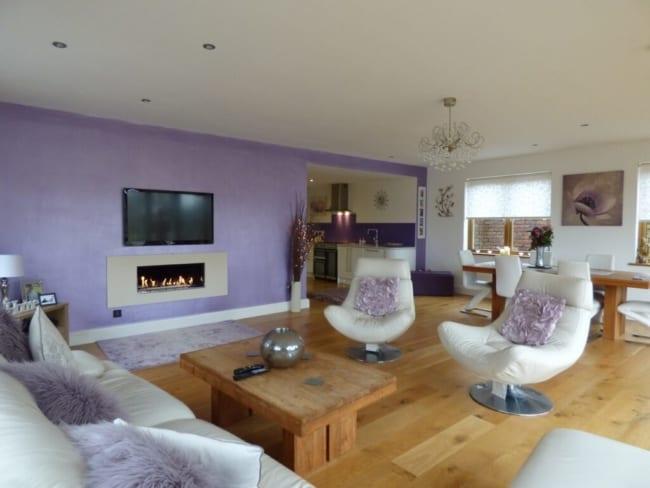 sala grande com parede lilás e sofá branco