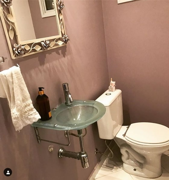 lavabo pequeno com paredes lilás e pia de vidro