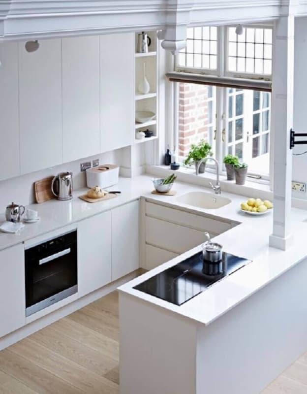 Cozinha americana planejada branca com janela na pia