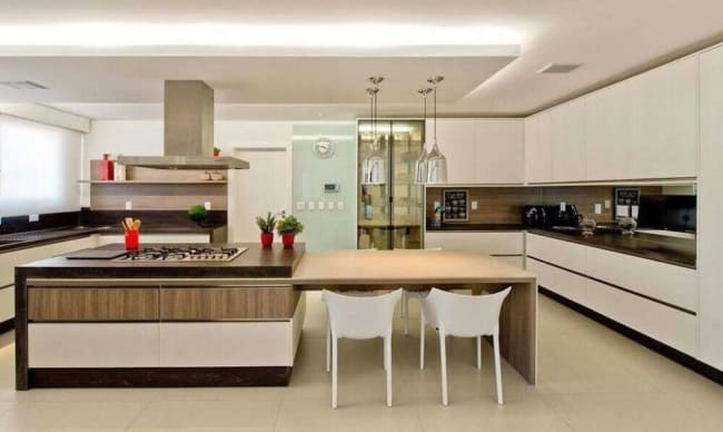Cozinha com ilha com cooktop e coifa