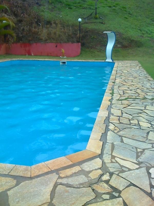 Sítio com piscina cercada por pedras mineiras