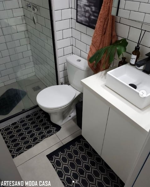 banheiro com tapetinhos preto e branco