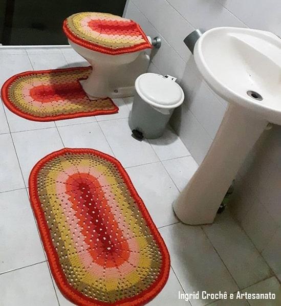 banheiro com conjunto de tapetes de crochê coloridos