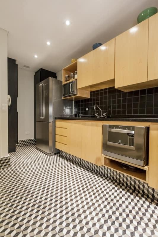 Cozinha com piso preto e branco e armários amarelos