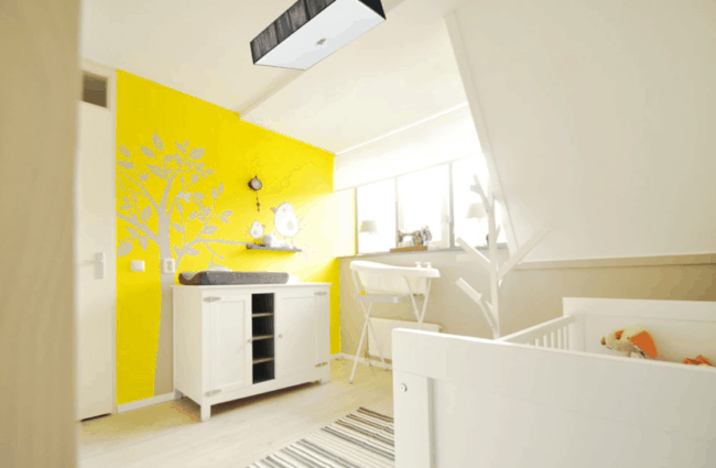 Quarto de bebê com parede amarela