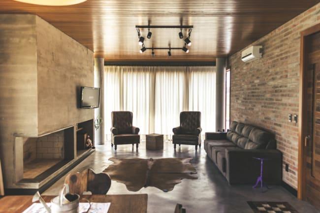 Sala com tijolinho com tapete de couro