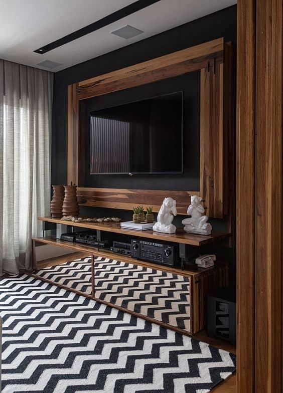 sala decorada em preto e móveis de madeira