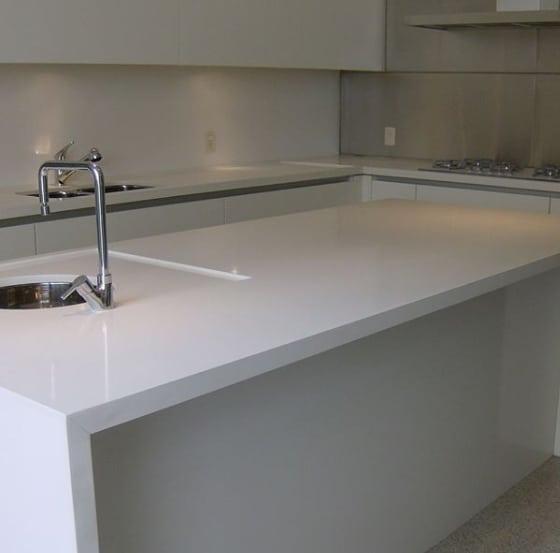 cozinha com ilha revestida de pedra branca