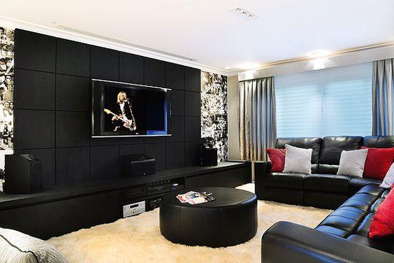 sala com sofá preto e almofadas vermelhas