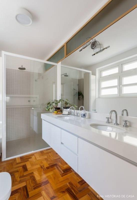 banheiro com piso de madeira e bancada de silestone branco