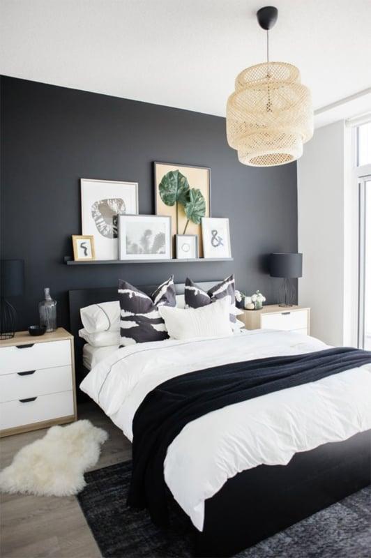 quarto decorado com parede preta e quadros