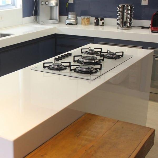 cozinha com ilha de silestone e fogão cooktop