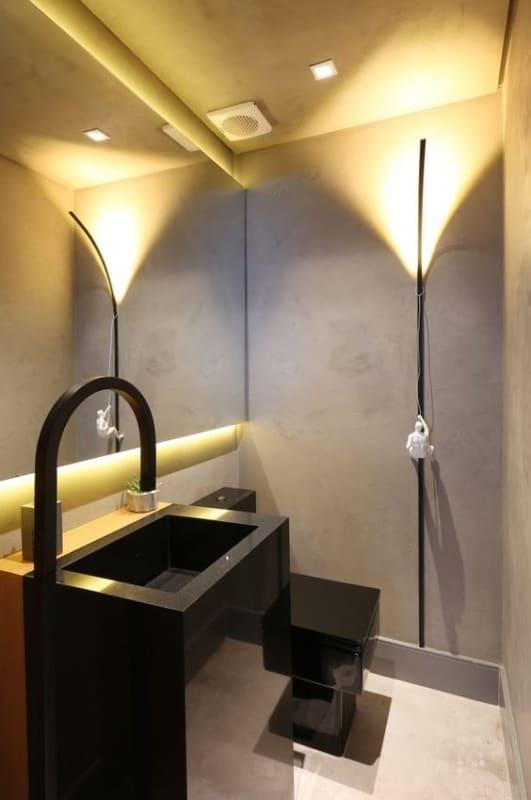 lavabo preto e com parede de cimento queimado