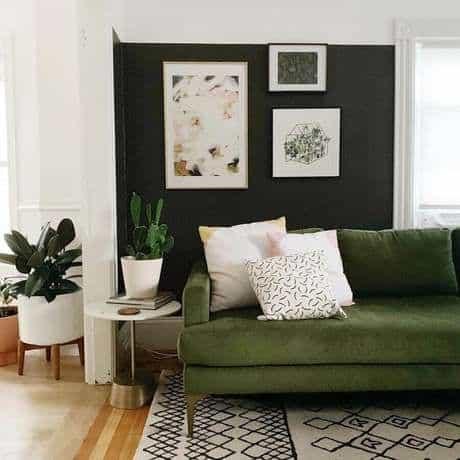 sala com parede preta e sofá verde