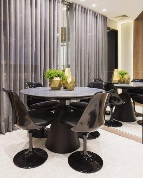 sala de jantar com mesa redonda e cadeira tulipa preta