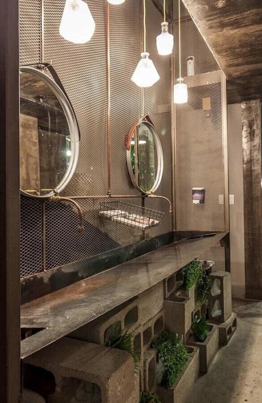 Banheiro masculino com estilo industrial com a pia com blocos
