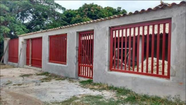 Construção e a faixada com muro e a grade vermelha