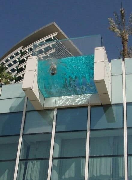 Visão de piscina no alto com parede de vidro