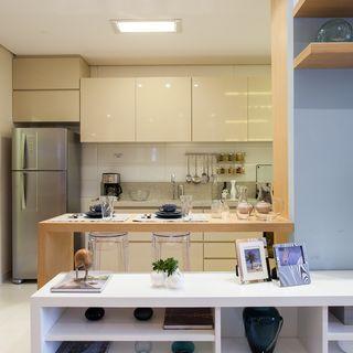 cozinha americana planejada com armários na cor creme
