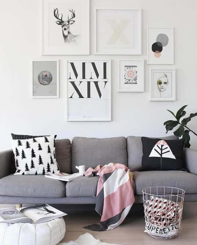 sala com sofá cinza e parede de quadros