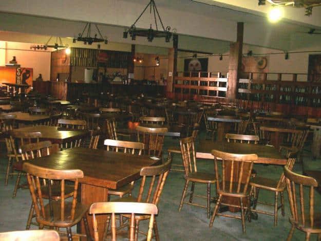 Restaurante amplo com cadeiras e mesas tradicionais