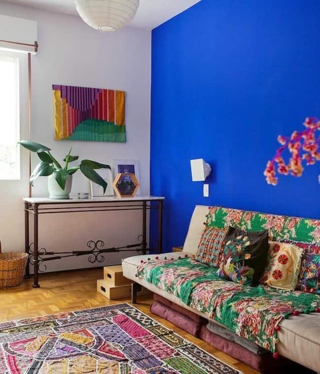 sala simples com parede azul royal e decoração colorida