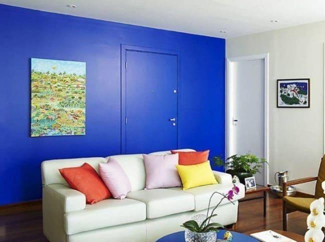sala com parede azul royal e sofá claro