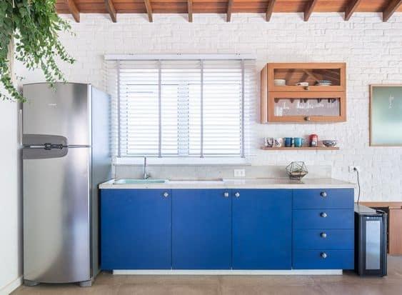 cozinha com parede de tijolinhos brancos e armário azul royal