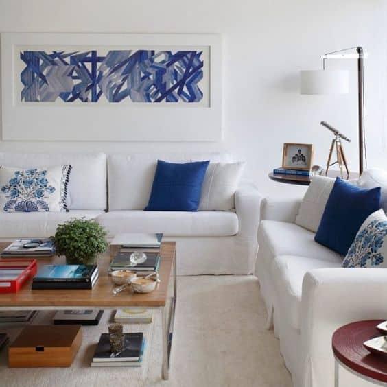 sala com sofás brancos e almofadas azul