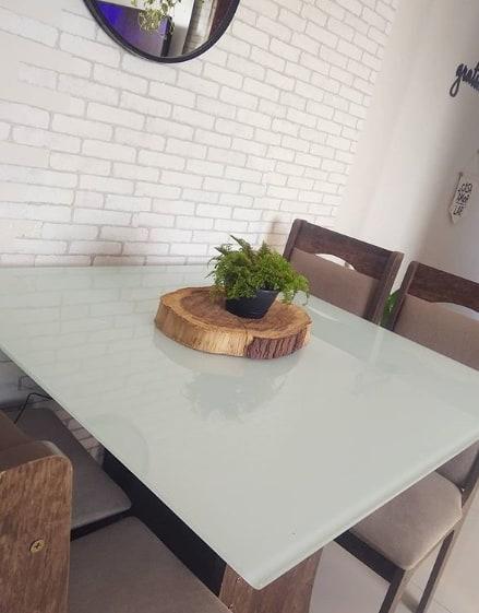 bolacha de madeira com vasinho de planta decorando mesa de jantar