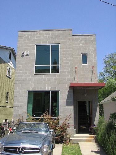 fachada de casa com blocos aparentes e janelas de vidro