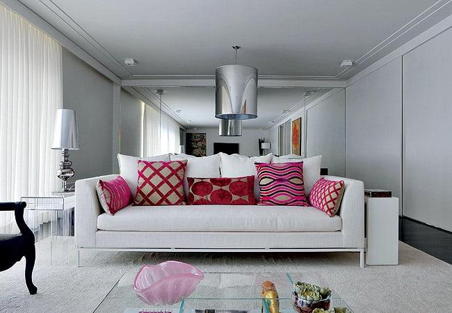 sala com sofá branco e almofadas vermelhas