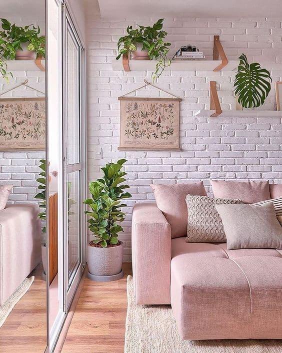 sala com parede de tijolinhos brancos e sofá rosa