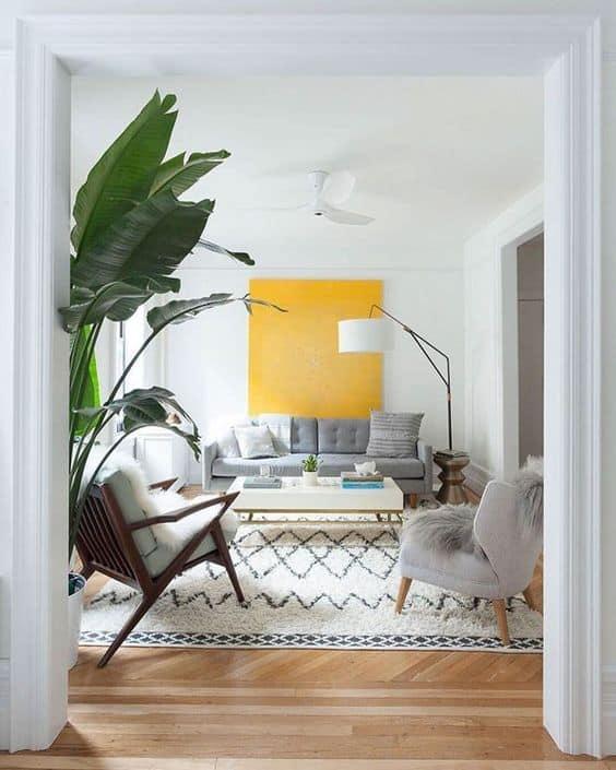 sala com parede branca e quadro amarelo
