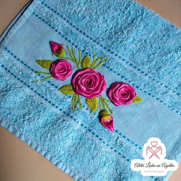 toalha azul com flores bordadas em fita
