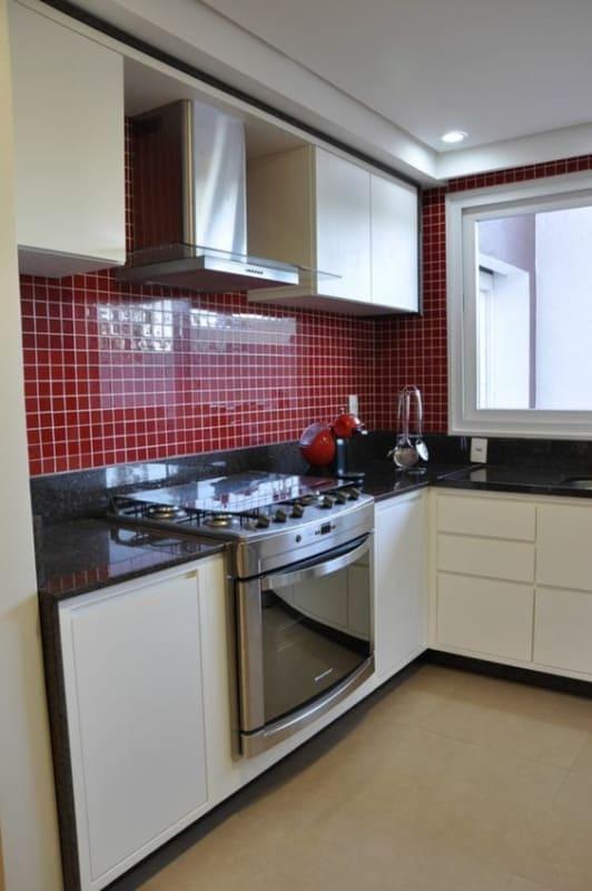 cozinha com armários brancos e parede de pastilhas vermelhas