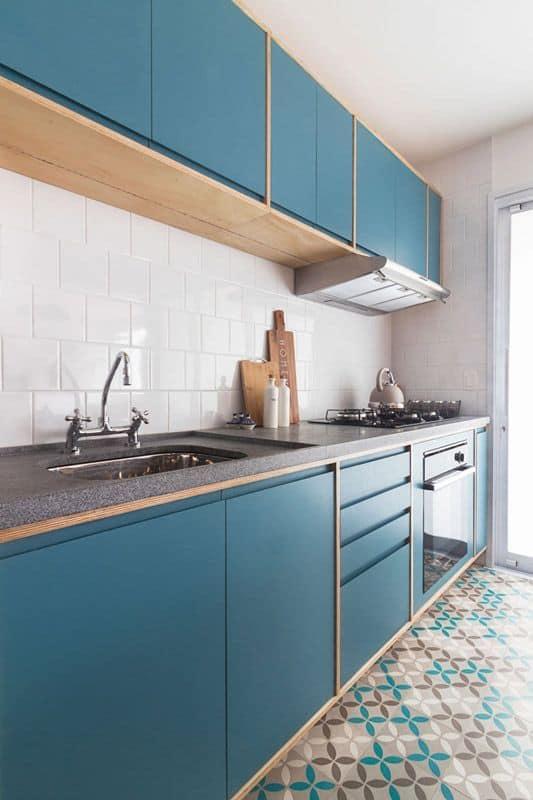 cozinha com azulejos brancos e armários azul
