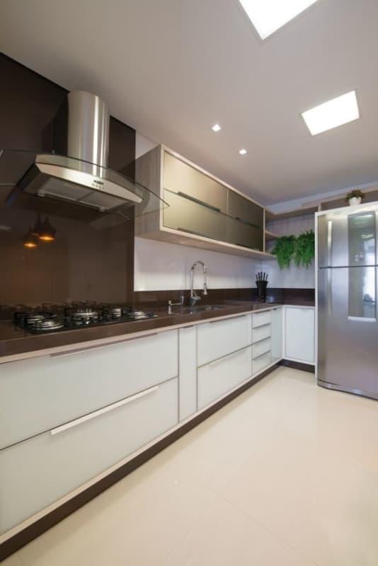 cozinha moderna com armários brancos e bancada marrom