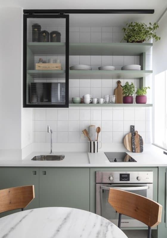 cozinha pequena com bancada branca e armários em verde claro