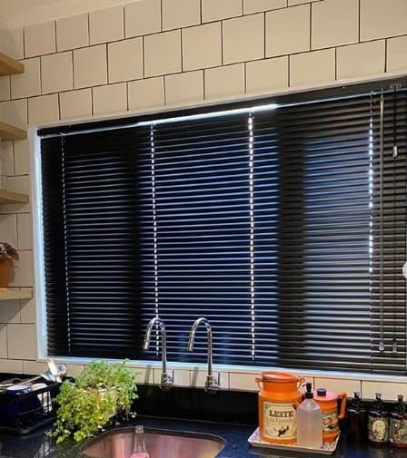 cozinha com revestimento branco e persiana de alumínio preto