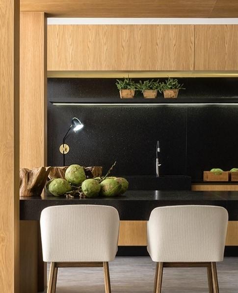 cozinha com armários de madeira e granito preto escovado