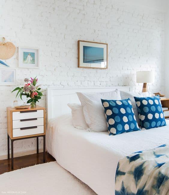 quarto branco com almofadas azul na cama